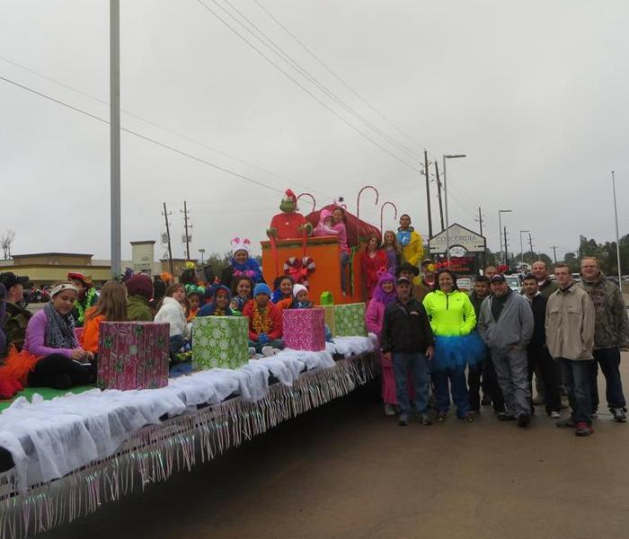 Trailer decorated with Christmas decorations and people surrounding the trailer and on trailer