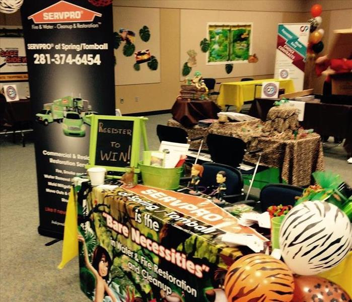 SERVPRO vendor exhibit. Table with servpro marketing items, servpro sign to the left and balloons to the right