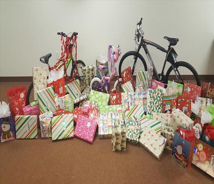 Christmas gifts wraped and placed on the floor infront of three bycicles