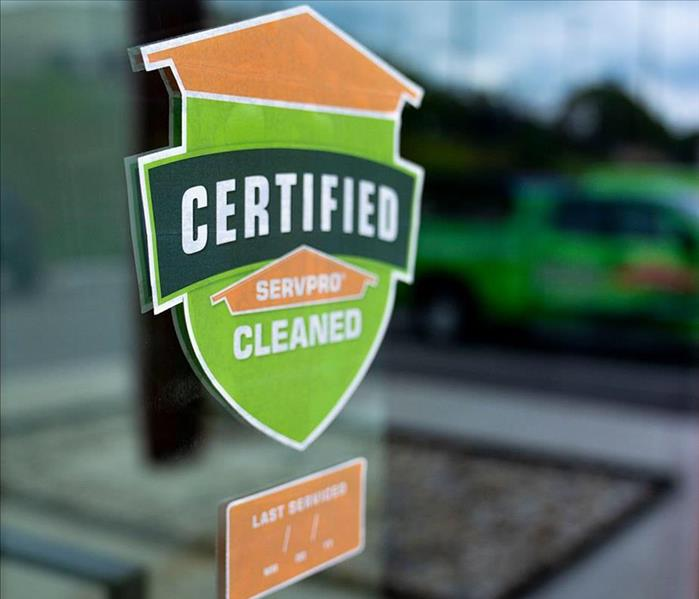 Certified: SERVPRO Cleaned sticker on window, sticker is the shape of a shield with orange and green color