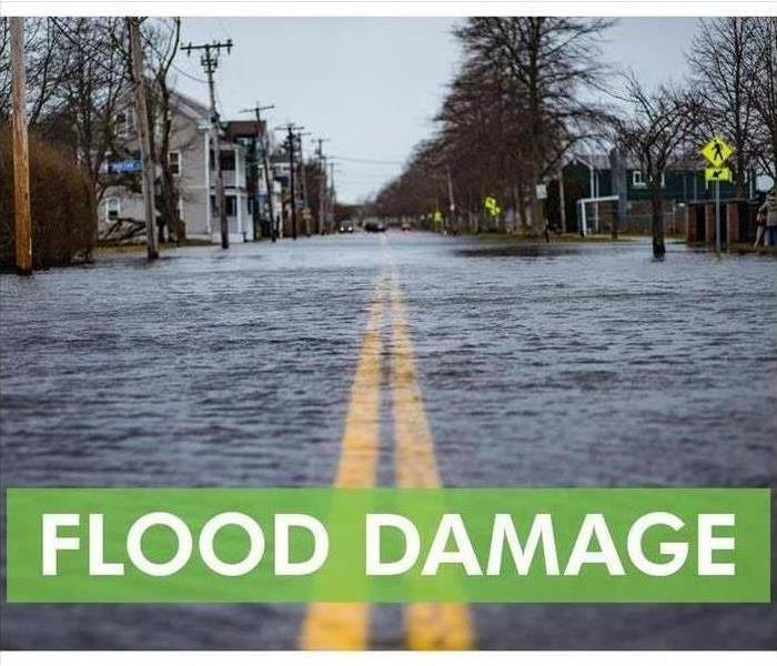 "Road covered with water, houses down sides on road. ""flood damage"" at bottom of the page."
