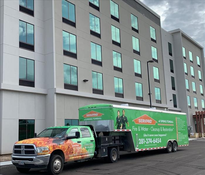 SERVPRO truck with SERVPRO trailer in front of large commercial building