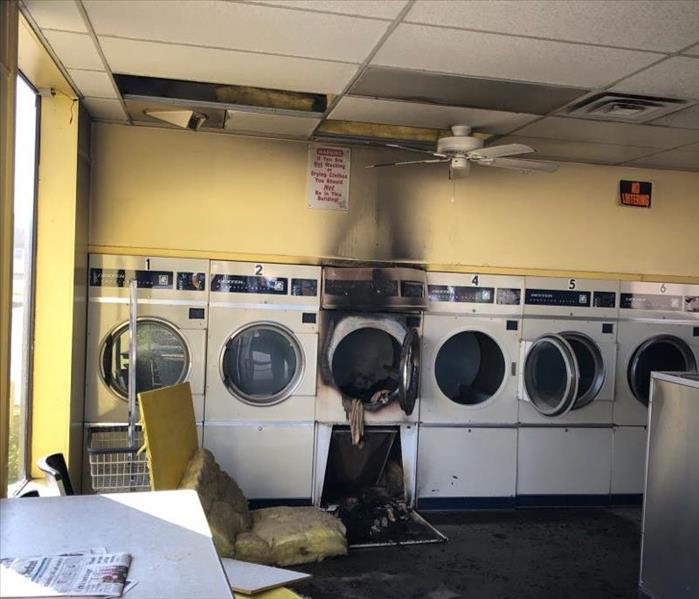 washateria with dryers along back wall, soot up wall, insulation on ground, one dryer burnt