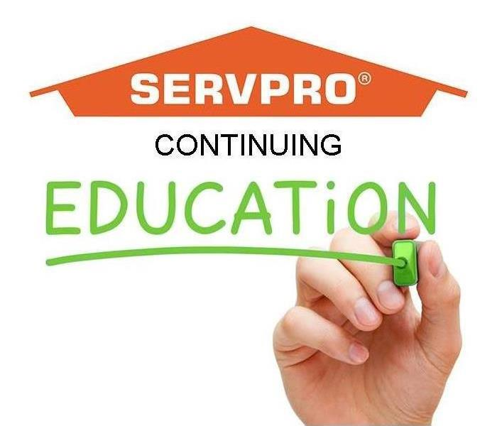 "Orange SERVPRO house with ""continuing education"" under it and a hand drawing a line under education"